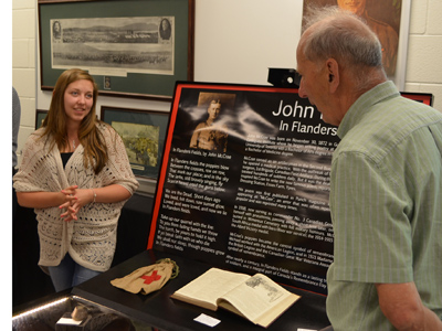 Grade 11 WDHS student Elizabeth Longley explains her John McCrae exhibit to visitors at the shool's museum.  Photo originally published for the Flamborough Review.  Credit Mac Christie