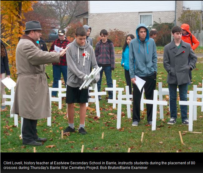 Facing History educator Clint Lovell and his students laying down crosses to commemorate fallen soldiers from Barrie, ON during WWI.  Photograph originally published in the Barrie Examiner.  Credit: Bob Bruton