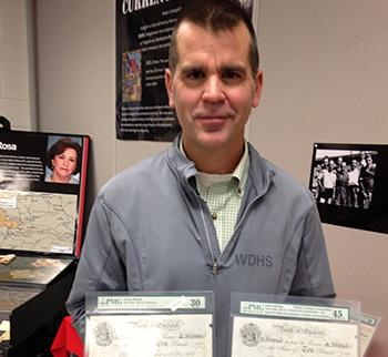 History teacher Rob Flosman with currency from Operation Bernhard. Photo by Abigail Cukier, published in The Canadian Jewish News.